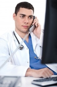 Portrait Of Male Physician Holding Receiver And Looking The Computer_by photostock